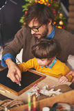 Drawing with chalk. Young men teaching son to draw with chalk Royalty Free Stock Image