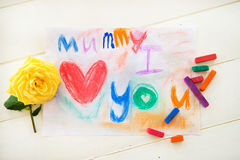Drawing from Child for Mummy. Little Girls Drawing with Pastels/ Chalks for Mothers Day. She wrote Mummy I Love You. Yellow Rose is laying nearby Royalty Free Stock Photo