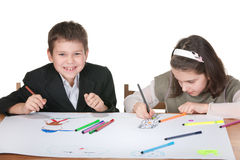Drawing class. Two children are drawing on the same big sheet of paper sitting at the desk; isolated on the white background Royalty Free Stock Images