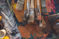 Drawing classes tools in art studio. Angle view photo of paintbrushes lying on palettewith oil paints brushstrokes Stock Images