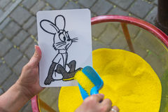 Drawing colored sand on a cliche. Educational activities for kids Royalty Free Stock Images