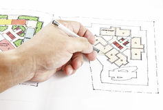 Drawing a colorful layout sketch of a building. A hand with a pen drawing a colorful freehand sketch of a building level royalty free stock images