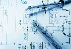 Drawing Compass. A closeup view of an architect's drafting table showing a blueprint and two compasses Royalty Free Stock Images