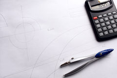Drawing compass and calculator on blueprint. Stock Photos