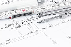 Drawing compass, folding rule, pen on architectural drawing Royalty Free Stock Photos