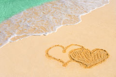Drawing connected hearts on beach Stock Photos