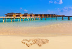 Drawing connected hearts on beach royalty free stock image
