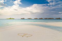 Maldives paradise beach and heart shapes drawing in sand. Moody landscape and sea on sky for holiday vacation background concept royalty free stock images