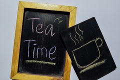 Drawing cup of tea and Tea Time on phrase colorful handwritten on blackboard stock photos