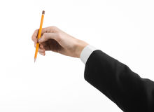 Drawing and Design theme: the hand of the artist in a black suit holding a pencil isolated on white background in studio Stock Image