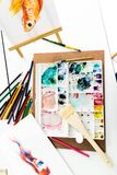 Palette, crayon and picture place on the white table. stock image