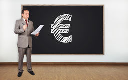 Drawing euro symbol. Businessman standing in office and drawing euro symbol on  blackboard Stock Photography