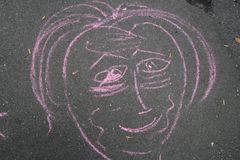 Drawing of a face shape in pink chalk. Pink chalk drawing of face on black tar walkway stock photo