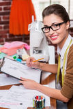 Drawing fashion sketch. Top view of beautiful young fashion designer drawing a fashion sketch and smiling at camera while sitting at her working place royalty free stock images