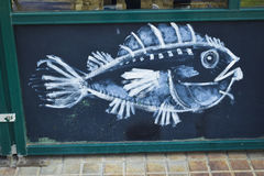 Drawing of a fish on a wall. Drawing on black background and white lines of a fish Royalty Free Stock Image