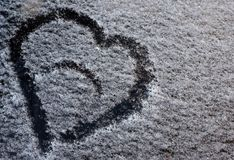 A drawing in the form of a heart on the fallen snow on the car glass royalty free stock photos