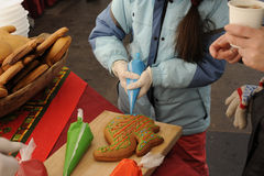 Drawing on the gingerbread. Girl decorate gingerbread colored glaze pastry bag Stock Photos
