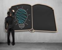 Drawing glowing lamp on book shape blackboard. Businessman standing and drawing glowing lamp on book shape blackboard stock photos