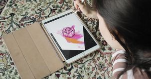 Drawing on a graphics tablet. Artist draws sketches at home. Top view stock footage