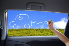 Drawing green car on the car windows. Hand drawing Electric car concept on the car windows stock images