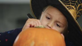 Drawing on halloween pumpkin. Little girl in witch costume drawing on pumpkin stock footage