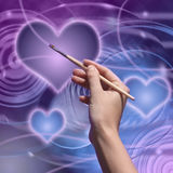 Drawing hand. The artist draws a love greeting card Stock Image