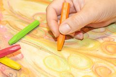 Drawing hand with crayons. Woman`s hand drawing abstract shapes with colorful crayons during art therapy royalty free stock photography