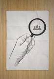 Drawing of hand holding magnifier glass Stock Photography