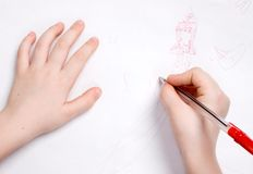 Drawing hands. The small child hands drawing princess on white paper Royalty Free Stock Photo