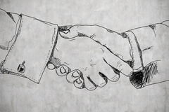 Drawing handshake. On a concrete wall Royalty Free Stock Images