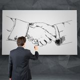 Drawing handshake on desk Royalty Free Stock Images