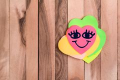 Cute heart happy emoji. Drawing happy emoji in heart shaped sticky note on wood background royalty free stock photo