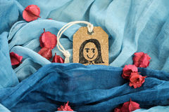 Drawing a happy girl on tag label put on blue scarf. royalty free stock photo