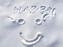 Drawing happy smiley face on snow in the winter time background, symbol Royalty Free Stock Images