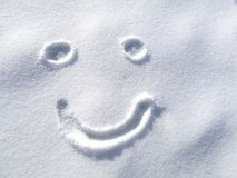 Drawing happy smiley face on snow in the winter time background, symbol Royalty Free Stock Image