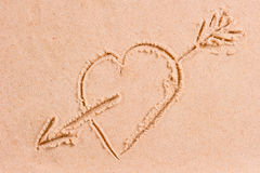 Drawing heart with an arrow on the wet sand Stock Photography