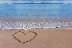 A drawing of a heart as a love symbol on a yellow sand at sea. A drawing of a heart as a love symbol on a yellow sand at a seascape background royalty free stock photography