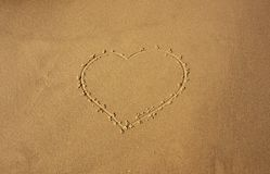 Heart depicted on sea sand for background royalty free stock images