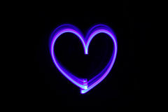 Drawing heart with light in the dark. Close up Royalty Free Stock Photography