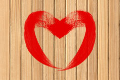 Drawing heart love symbol on yellow wooden wall Stock Image