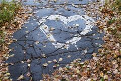 Drawing heart on the pavement. Dry leaves. Wet path. Dark asphalt Stock Images
