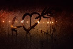 A drawing of a heart pierced by Cupid`s arrow on the sweaty glass of the car in backlit city lights.  stock image