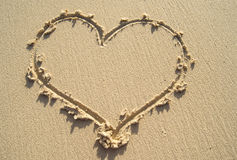 Drawing heart on sand beach. Stock Images