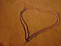 Drawing of a heart on sandy be. Ach after the water has pulled back from the sand royalty free stock images