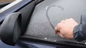 Drawing a heart shape on side door car window with a finger. Drawing a heart shape with a finger on side door car window covered with hoarfrost stock video footage