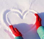 Drawing heart on snow Stock Photo