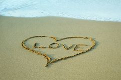 Drawing heart symbol on the sand background at the beach stock photo
