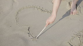 Drawing heart symbol on a sandy beach stock video footage