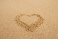 Drawing a heart on wet golden beach sand Royalty Free Stock Photo