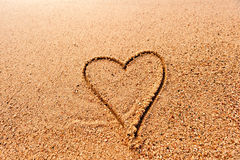 Drawing a heart on the wet sand at the sea Stock Photos